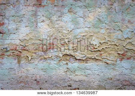 background texture old brick wall with remnants of colored plasters