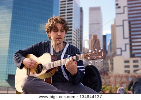NEW YORK - MARCH 17, 2016: man play guitar at Pier 15 at daytime. Pier 15 is located east of South Street and FDR Drive in Lower Manhattan, New York City.