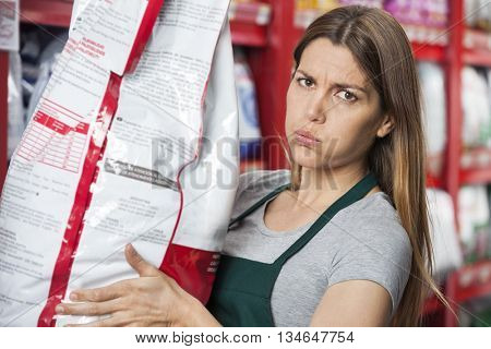 Saleswoman Carrying Heavy Food Package In Pet Store