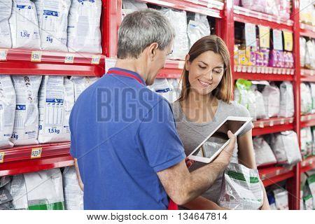 Woman Looking At Salesman Using Digital Tablet In Pet Store