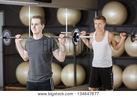 Friends Lifting Barbell While Standing In Gym