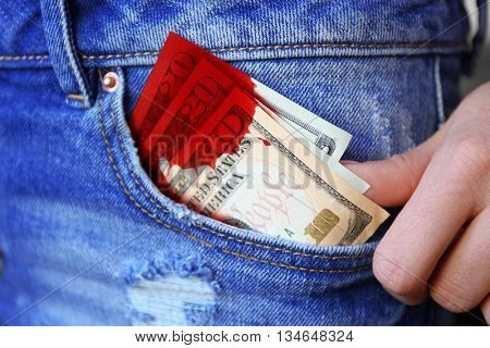 Dollar banknotes with bloodstain in jeans pocket closeup