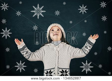 Little girl in a trendy knitted clothes looking up and drawn snowflakes on blackboard background