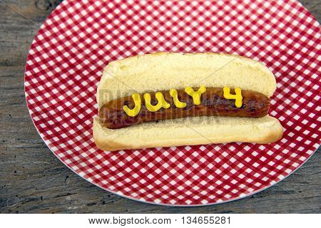 Forth of July hot dog with yellow mustard in a bun on red and white gingham plate on rustic wood.