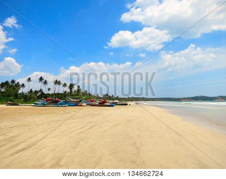 Empty wide clean beach with palms and fishing boats, Weligama, Sri Lanka