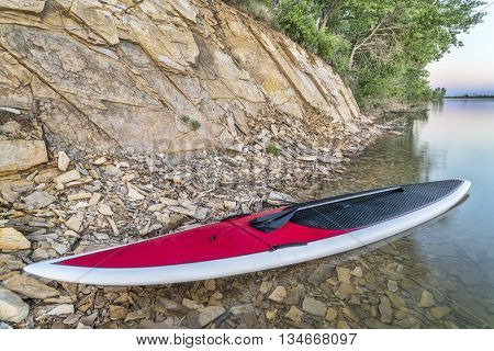 red stand up paddleboard with a paddle on a lake shore with a rocky cliff  -Boedecker Reservoir near Loveland, Colorado