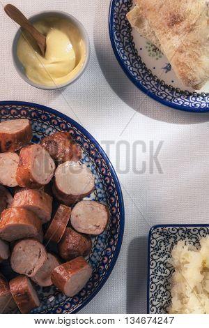 Sausage and sauerkraut on traditional Polish pottery,