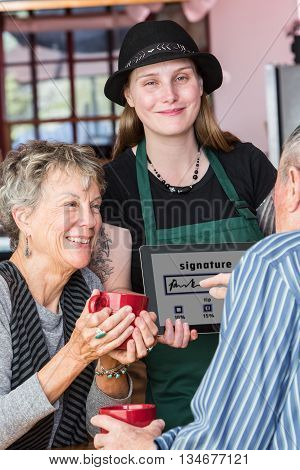 Woman Watching Man Write Signature On Tablet