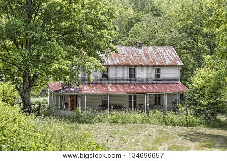 An old farmhouse with a large porch stands abandoned along a county road in rural West Virginia.