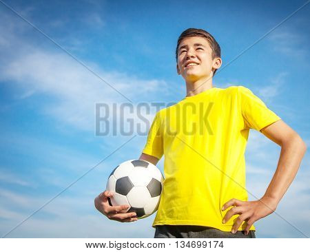 Happy Teenage Boy With A Soccer Ball On A Background Of Blue Sky