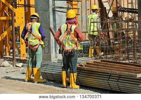 MALACCA, MALAYSIA -MARCH 13, 2016: Construction workers at the construction site in Malaysia. All of them is required to wear adequate safety equipment during works to make sure their safety.