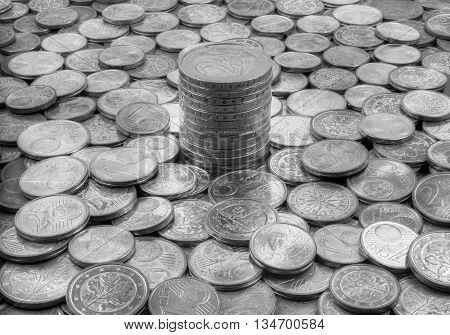 Stacked euro coins in the middle of  other coins
