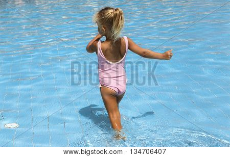 Beautiful little girl in a blue swimming pool water