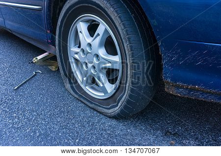 Blue car with flat tire on the road. Flatten tyre