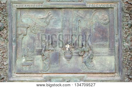 PISA, ITALY - JUNE 06, 2015: PISA, ITALY - JUNE 06, 2015: The Annunciation of the Virgin Mary, detail of the central door of the Cathedral St. Mary of the Assumption in Pisa, Italy on June 06, 2015