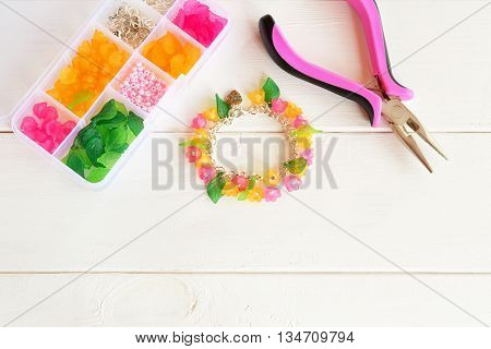 Bright beautiful hand bracelet with pink and yellow acrylic beads flowers and green leaves. Pliers. Organizer with beads, plastic flowers and metal elements for jewelry on white wooden background