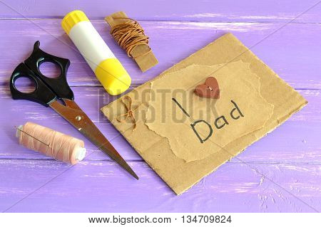 Hand greeting card with message I love dad. Homemade design fathers day card. Happy birthday card for dad. Scissors, glue, cord, thread, needle. Craft inspirations for kids. Lilac wooden background
