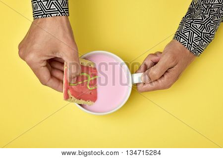 high-angle shot of a young caucasian man soaking a pink biscuit in a pink milkshake, on a yellow surface