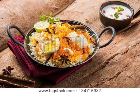 Basmati rice slowly cooked with Masala roasted egg and spices served in kadhai or kadai with yogurt dip, selective focus, egg biryani or anda rice or egg rice