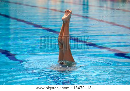 Synchronized swimmer legs movement. Synchronized swimmer performing a synchronized routine of elaborate moves in the water.
