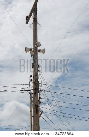 Speakers on electric pole with a blue sky background