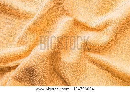 Closeup surface wrinkled orange napkin fabric background