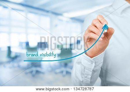 Brand visibility improvement concept. Brand manager (marketing specialist) draw growing graph with text brand visibility office in background.