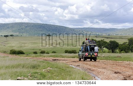 AFRICA, KENYA, MAY, 05, 2016 - Through the Masai Mara National Park Jeep carries local African residents, who crowd into the car in extreme quantities. Kenya, Africa