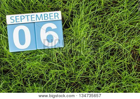 September 6th. Image of september 6 wooden color calendar on green grass lawn background. Autumn day. Empty space for text.