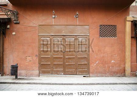 Folding door closed. wooden door closed, small shop.