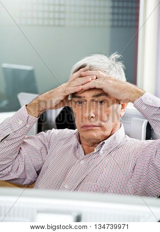 Tensed Senior Student Looking At Computer In Classroom