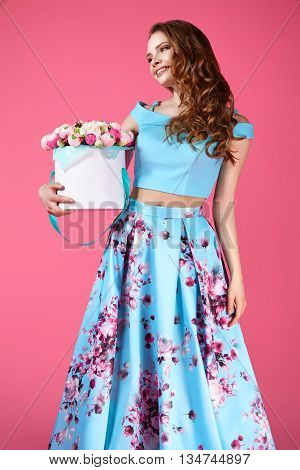 Young pretty girl standing and holding white box with paper flowers. Vogue fashion style studio portrait of sexy girl in a blue dress with flowers pattern.