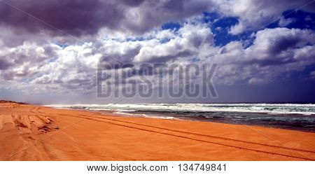 Horizontal landscape of the beach with  tyre track in the foreground and dramatic clouds (Stockton Beach, NSW, Australia)