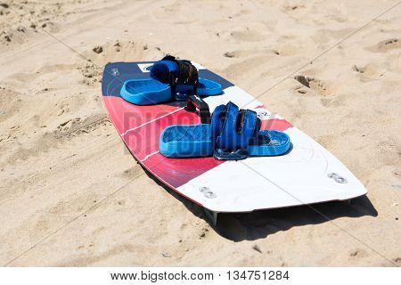 Windsurfing board with sail lying on the sand and windless sea