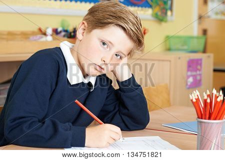 Bored Male Elementary School Pupil At Desk