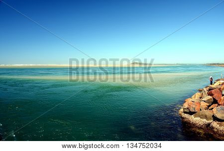 Fisherman at Harrington beach. Long sand reef in the background.