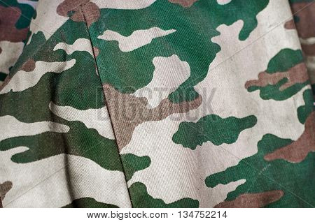 Camouflage fabric texture background. Soft selective focus and shallow depth of field