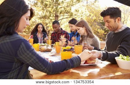 Friends at a table at a barbecue saying grace before eating