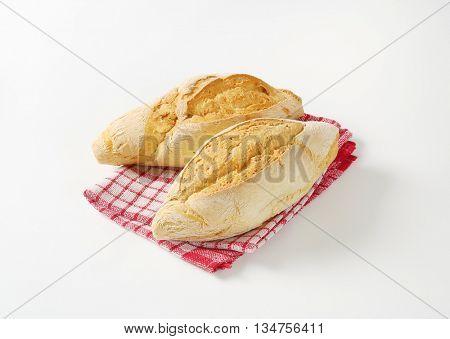 fresh diamond shaped ciabatta bread on checkered dishtowel