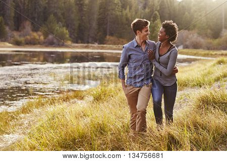 Mixed race couple embracing, walking near a rural lake