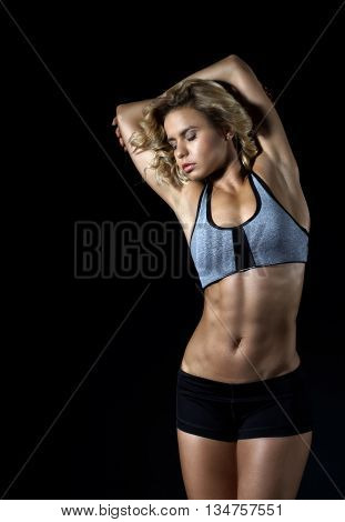 Sport young fitness girl with slim muscular body posing in the studio on a dark contrast background. Girl dressed in athletic shorts and top. Looking to the side