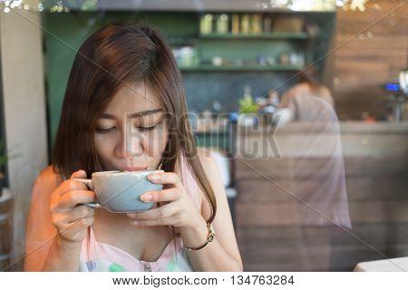 beautiful girl drinking hot coffee or tea in coffee cafe model asia women female of thai people
