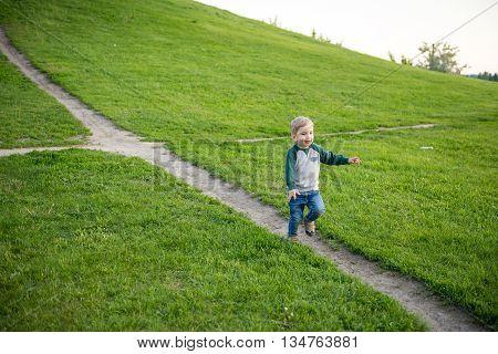 kid walks in the park. In summer, a little boy is walking on the green grass in the summer. Cheerful kid blondingulyaet in summer park.