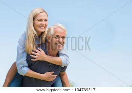 Senior man giving piggyback ride to happy woman against blue sky.  Smiling mature woman piggyback on senior man. Retired couple having fun and thinking.