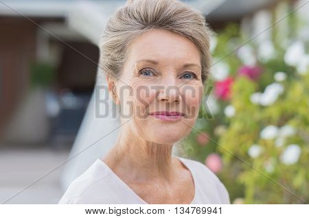 Portrait of a happy old senior woman looking at camera. Outdoor portrait of smiling retired woman. Close up face of a smiling elderly woman ouside the house.