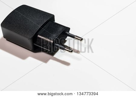 Black USB-Charger on a white acryl background.