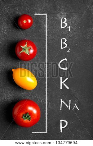 Fresh red and yellow tomatoes on the black chalkboard (vitamins and minerals in 100 gramm of product)in 100 gram of product)