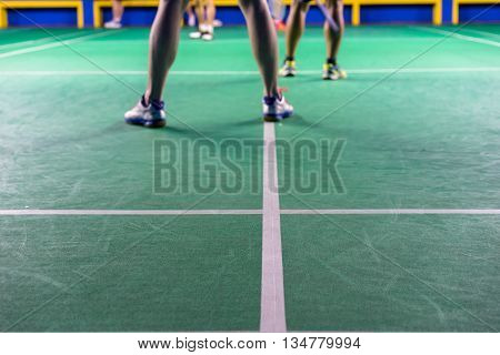 Legs Of Male Doubles Badminton Players Playing Double Badminton Game In A Badminton Court. Focus On