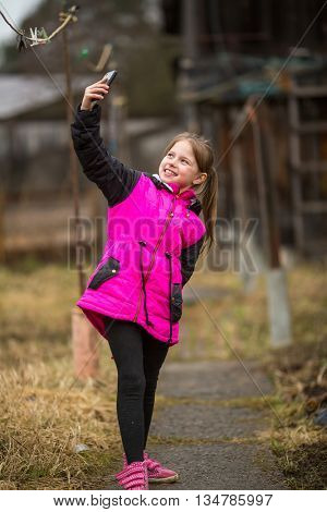 Little girl makes selfie on the phone in the yard of the farmhouse.