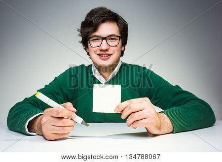 Smiling oung man in green pullover sitting at white desk with blank paper sticker and marker in hand